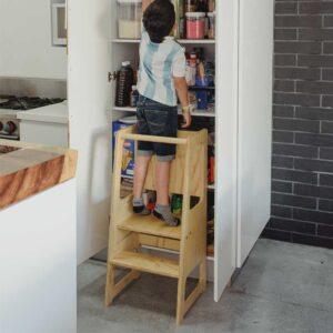 niño de 8 años en torre de aprendizaje madera de 3 niveles con pizarron