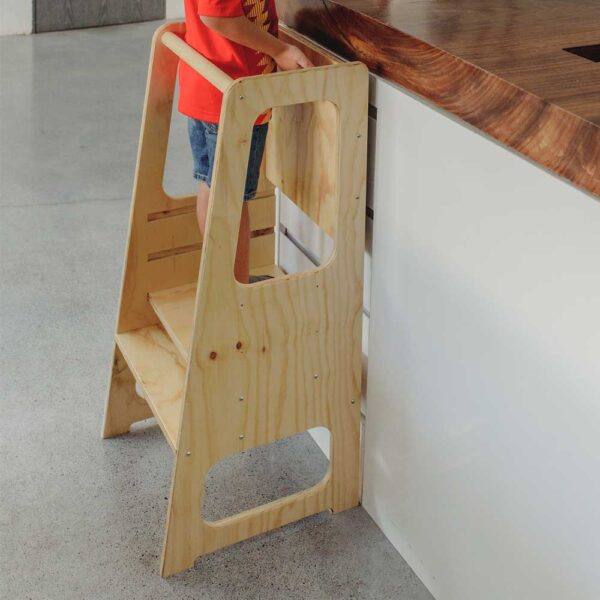 niño de 7 años en torre de aprendizaje de 3 niveles con pizarron