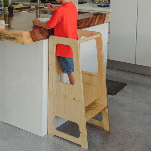 niño de 8 años en torre de aprendizaje de 3 niveles con pizarron